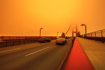 Cars crossing Golden Gate Bridge from Presidio to north. Smoky orange sky the bridge of San Francisco city for California fires in in America. Composition about wildfires and climate change concept.