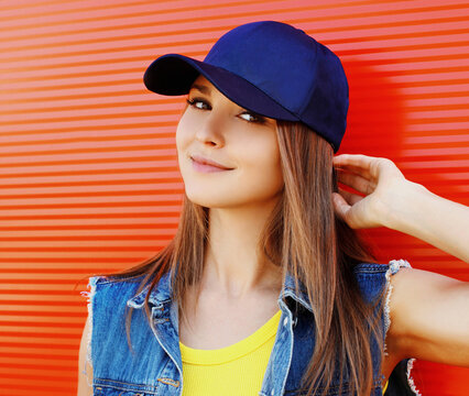 Close up summer portrait of attractive young woman wearing a blue baseball cap in the city