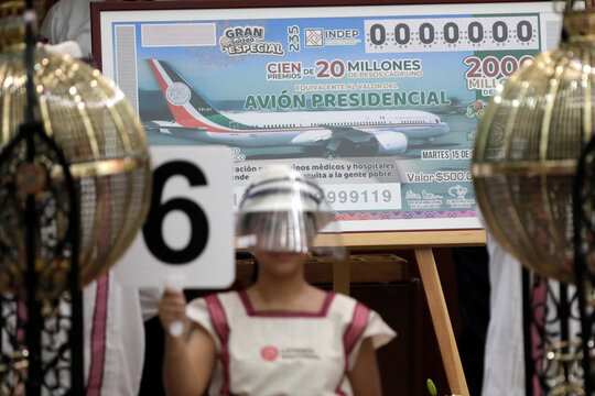 A girl holds a sign with the number 6 during a lottery raffle for the value of the last president's luxury plane at the National Lottery building in Mexico City