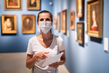 Focused adult girl in disposable face mask admiring paintings in museum holding brochure with exhibition program
