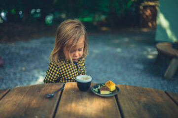 Preschooler drinking coffee and eating cake in outdoor cafe