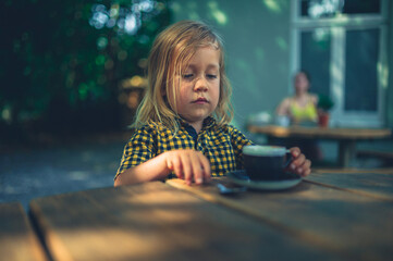 Preschooler drinking coffee at at table outdoors