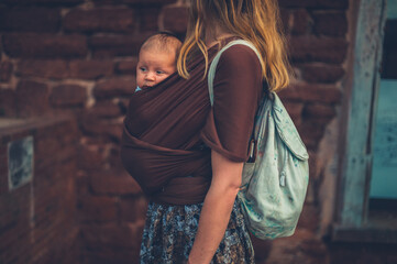 Young mother with her baby in a sling carrier