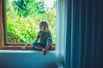 Preschooler sitting on window sill