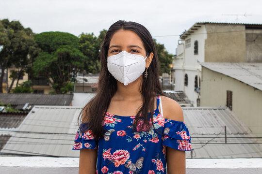 Niña latina con mascarilla pensando desde su balcón
