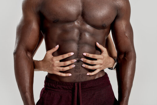 Perfect abdomen. Female hands embracing, touching muscular african american man abs isolated over grey background. Sports, workout, bodybuilding concept