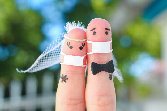 Fingers art of happy couple in medical mask from COVID-2019. Concept of wedding ceremony.