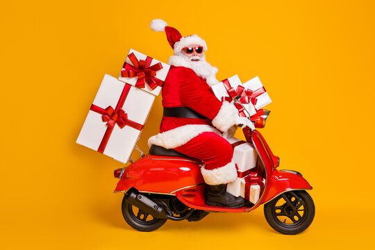 Full size profile side photo of white grey hair bearded santa claus ride motorbike deliver x-mas christmas gifts on noel night wear headwear isolated bright shine color background