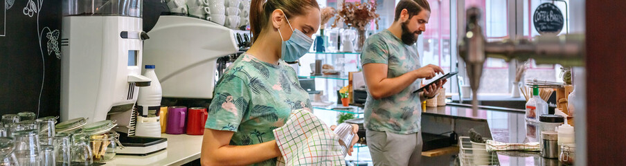 Waitress with mask cleaning glasses in a coffee shop while her coworker works with a tablet