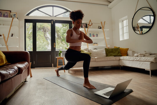 Healthy african woman watching video on laptop while exercising with hands joined on yoga mat at home