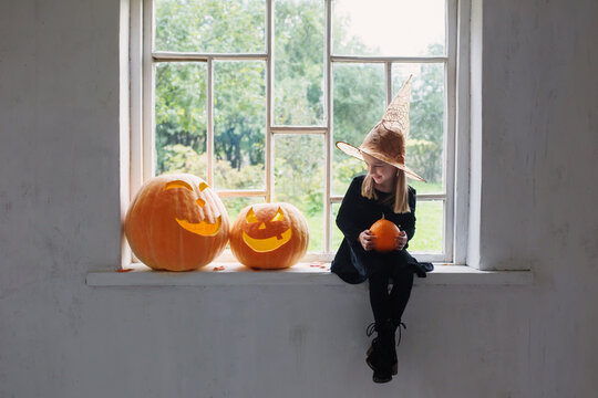 little witch in black dress with halloween pumpkins on windowsill