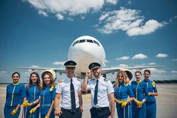 Cheerful airline workers standing in airfield under blue sky Fotobehang