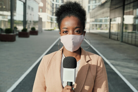 Portrait of African young reporter in protective mask holding microphone and looking at camera while standing in the city