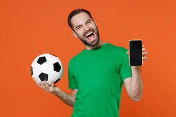 Overjoyed young man football fan in green t-shirt cheer up support favorite team with soccer ball hold mobile phone with blank empty screen isolated on orange background. People sport leisure concept.