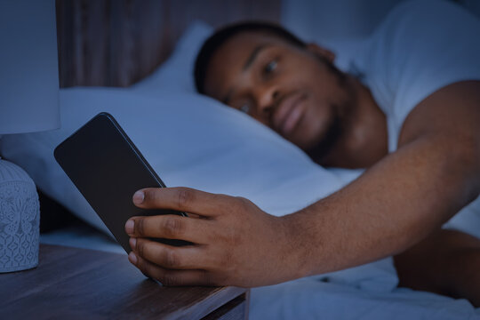 Guy Reading Message On Phone Lying In Bed At Night