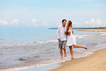 Attractive couple of sweethearts have fun on the sea coast