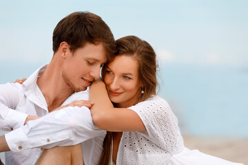 Portrait of a sweet couple of young lovers resting on the beach
