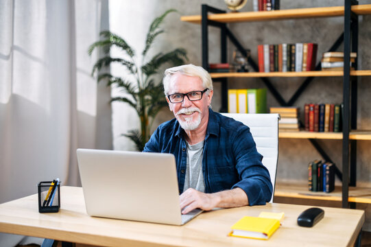 Handsome senior man in smart casual wear and eyeglasses is using a laptop at contemporary office, he is looking at camera and smiling