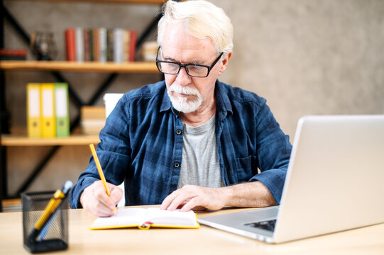 Mature man in casual wear and eyeglasses is using a laptop computer for online studying at home office. A gray-haired man is writing in notebook while sitting and watching webinars, online classes
