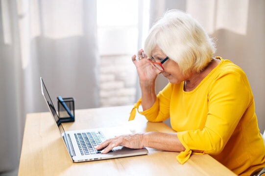 A senior concentrated business lady staring at the screen and lowered her eyeglasses while using laptop. Side view