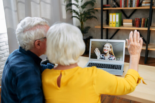 Grandparents have online meeting with a granddaughter. A grandfather and a grandmother are using laptop for video call. Back view