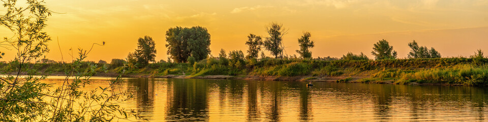 Picturesque summer panoramic landscape with riverbank at sunset. Calm plain river, reflection in water. Wonderful nature, beautiful natural background. Akhtuba river, Astrakhan region, Russia