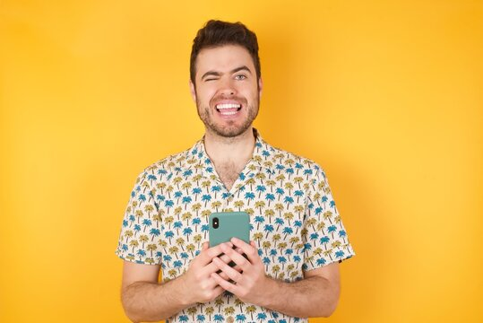 Young man holding pineapple wearing hawaiian shirt over yellow isolated background taking a selfie celebrating success