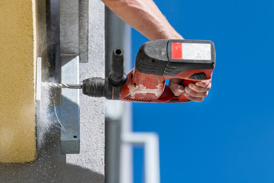 Working power hammer drill. Anchoring of steel construction into building masonry. Hand holding cordless drilling machine. Fixing and mounting of guard rail on terrace or balcony. Falling dust detail.