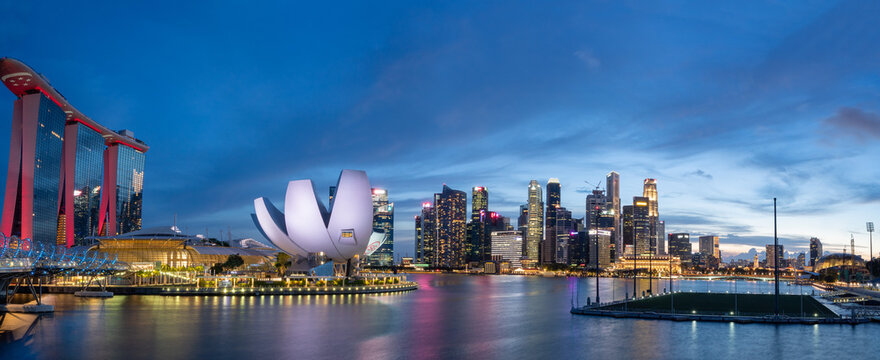 Wide panorama of Cityscape of Singapore Marina bay area at dusk.