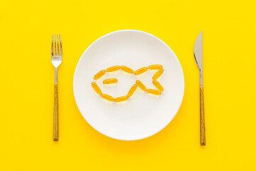 Omega cod liver oil capsules on plate with fish shape, top view