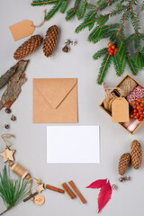 Christmas holiday background with Natural wooden decorations, pine cones, empty blank card, paper envelope and branches on gray paper