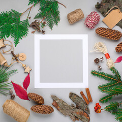 Christmas holiday background with Natural wooden decorations, empty frame, pine cones and branches on gray paper.