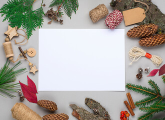 Christmas holiday background with Natural wooden decorations, empty white paper, pine cones and branches on gray.