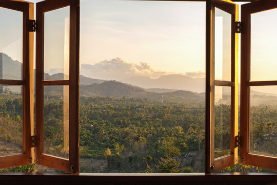 View from the window to the fields and mountains at sunset. View from the hotel window in the north of Bali