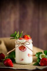 sweet homemade yogurt with ripe fresh strawberries in a jar