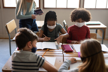 Group of kids wearing face masks studying in class at school