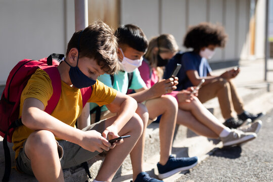 Students wearing face masks using smartphones while sitting in school playground