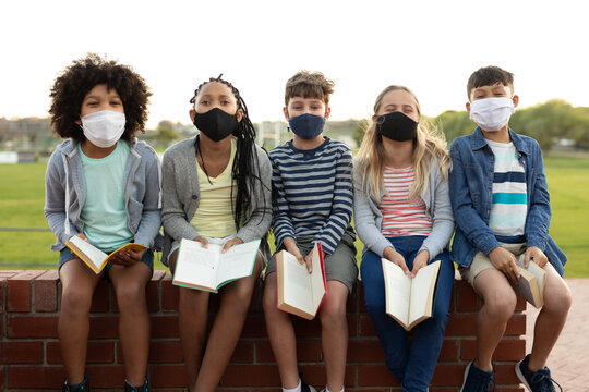 Portrait of group of kids wearing face masks with books sitting on a brick wall