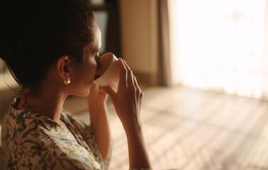 Woman enjoying refreshing coffee at home