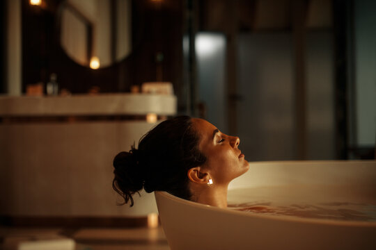 Young woman with eyes closed relaxing in bathtub
