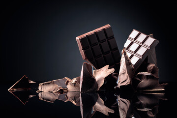 A broken chocolate bar and pieces of dark chocolate on a black reflective background.
