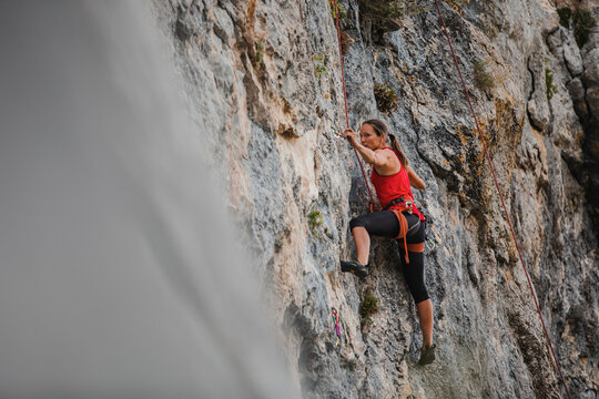 Confident female rock climber climbing mountain