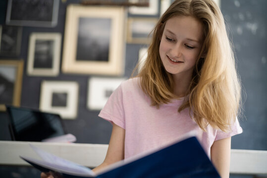 Girl reading in excersice book at home