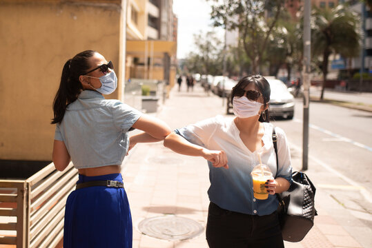 Female friends wearing sunglasses and masks giving elbow dump while standing in city