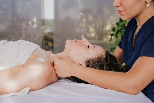 Close-up of female therapist massaging customer's neck on table in health spa