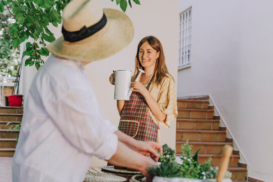 Senior woman wearing hat looking at daughter holding watering can against house in yard