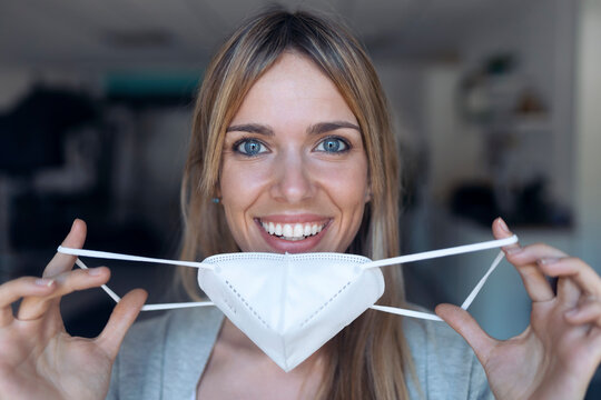 Portrait of smiling young woman putting on protective mask