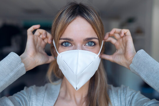 Portrait of young woman putting on protective mask
