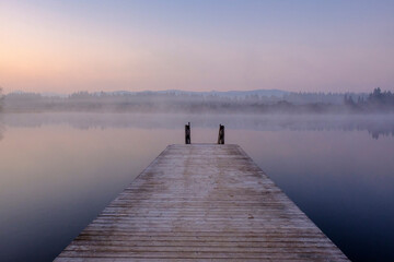 Jetty on shore of Kirchsee lake at foggy dawn