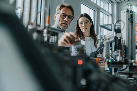 Male scientist with young woman examining machinery in laboratory